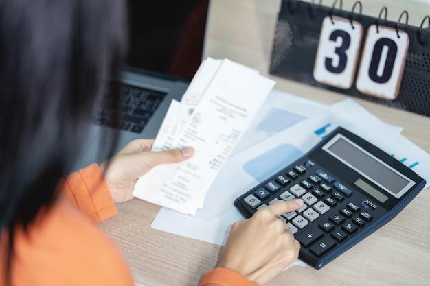女性は電卓を押して、金融と収入を扱うためのコスト法案を計算します。 Premium写真