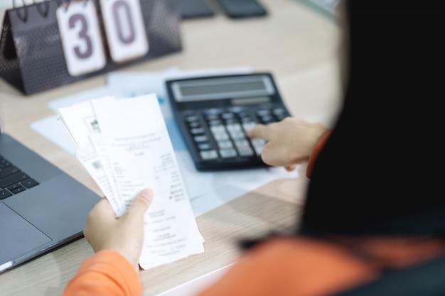 Женщина, держащая счет и использующая калькулятор, и вычисляющая стоимость счета и оплаты. Premium Фотографии
