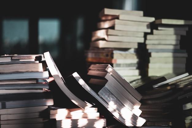 木製のテーブル、学習および教育の概念に関する古書のスタック。セレクティブフォーカス Premium写真
