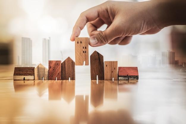 木のテーブル上のモデルからミニ木の家モデルを選択する手 Premium写真