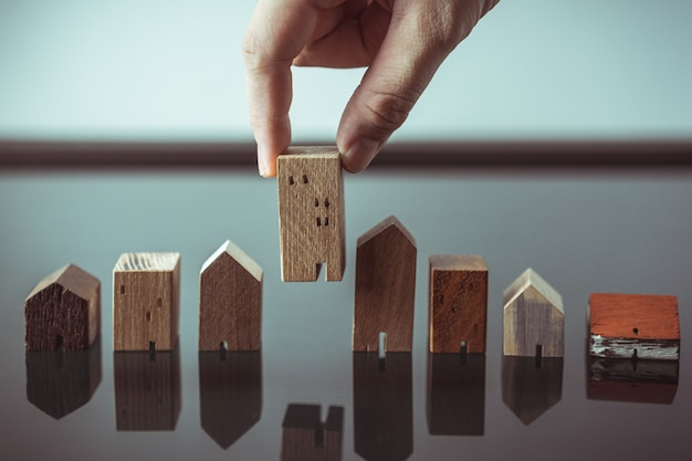 モデルと木製のテーブルの上のコインのお金の行からミニ木製家モデルを選択する手 Premium写真