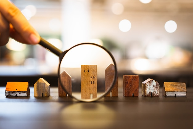 虫眼鏡を押しながら家のモデルを見て手 Premium写真