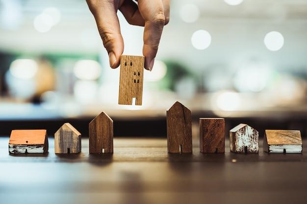 木製テーブルのモードからミニ木製家モデルを選択する手 Premium写真
