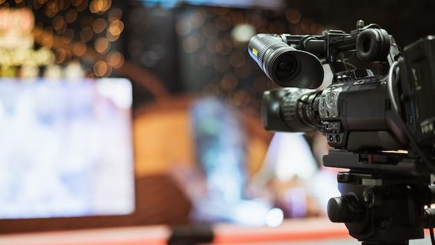 Видеокамера принимая потоковое видео в реальном маштабе времени с людьми работая предпосылка на конференц-зале. Premium Фотографии