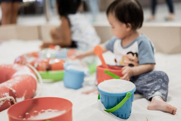 Счастливый маленький азиатский мальчик с красочной игрушкой на пляже песка, сезоне лета. Premium Фотографии