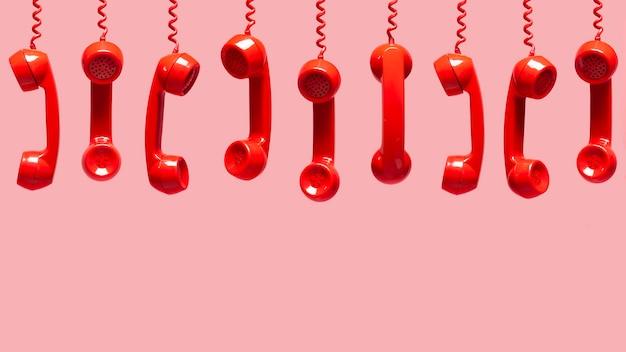 Различные виды старых красных телефонных приемников висит на розовом фоне Premium Фотографии