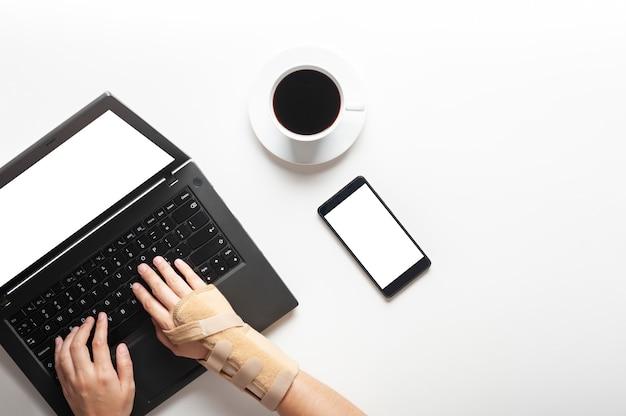 コンピューターを使用してから手首の痛みと手の上から見る Premium写真