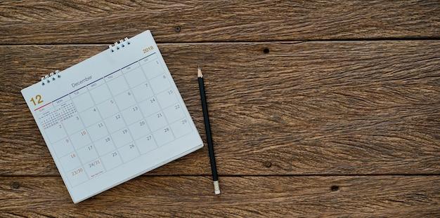 Карандаш и календарь на фоне дерева Premium Фотографии