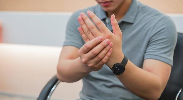 ハードワークからの救済の痛みのために彼の手と腕にマッサージの男 Premium写真