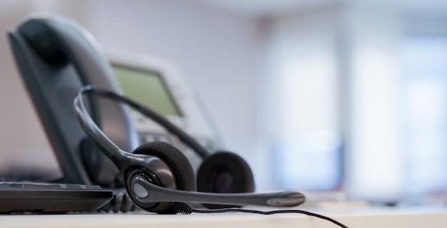 Закрыть на колл-центр гарнитуры с телефоном в офисе, концепция мониторинга операционной комнате Premium Фотографии