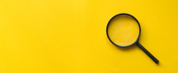 黄色の背景に拡大鏡ガラスを閉じる Premium写真