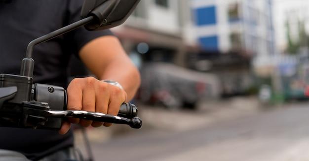 道路にオートバイに乗るためのオートバイの男の手のタッチハンドルを閉じる Premium写真