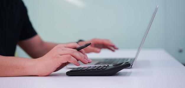 管理費の概念のための電卓の従業員男指押しにクローズアップ Premium写真