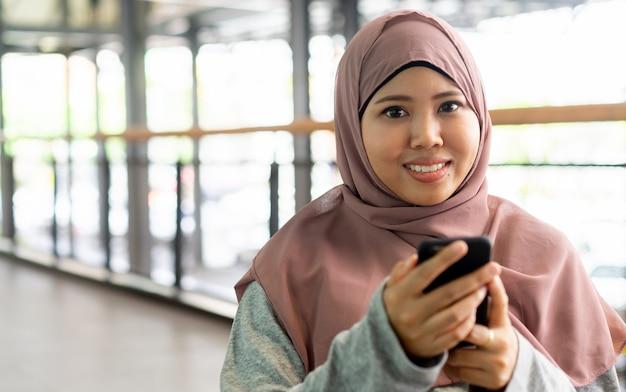 Закройте вверх по мусульманской улыбке женщины и держите мобильный телефон в расслабляющем времени, концепции людей образа жизни Premium Фотографии