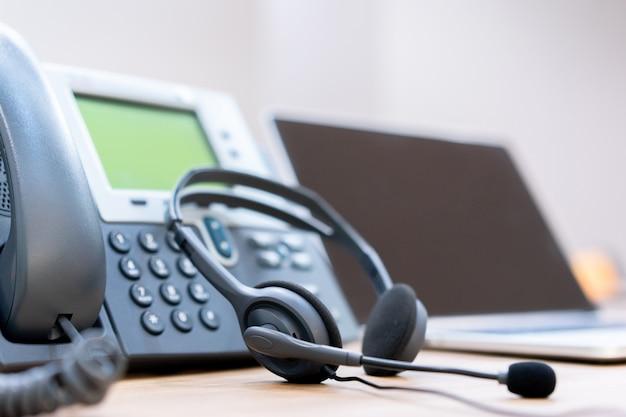 Мягкая фокусировка на гарнитуре с телефонными устройствами на офисном столе для поддержки клиентов Premium Фотографии