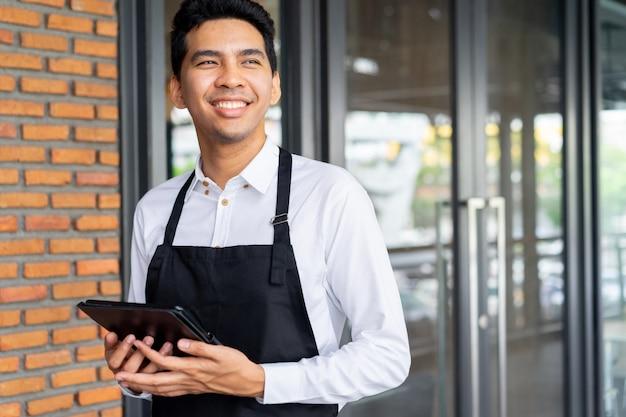 タブレットを保持しているとコーヒーカフェショップの外に立っている男バリスタ Premium写真