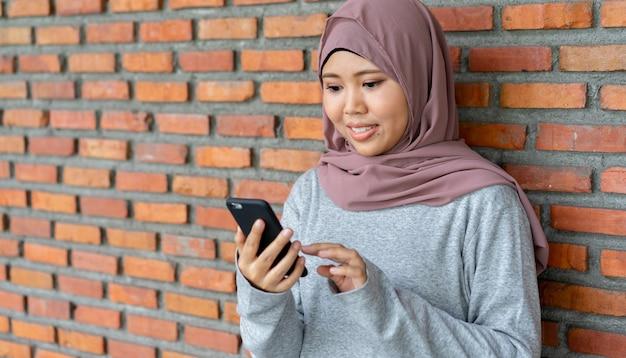 Азиатская мусульманская женщина, держащая смартфон для покупок в интернете Premium Фотографии
