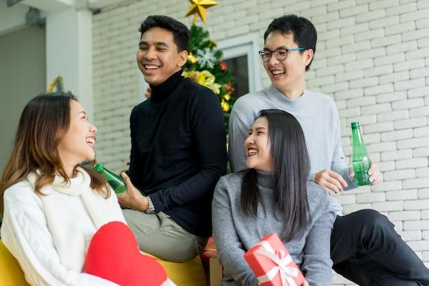 パーティーとメリークリスマスの装飾が施されたリビングルームで一緒に笑って笑って若い大人の友人 Premium写真