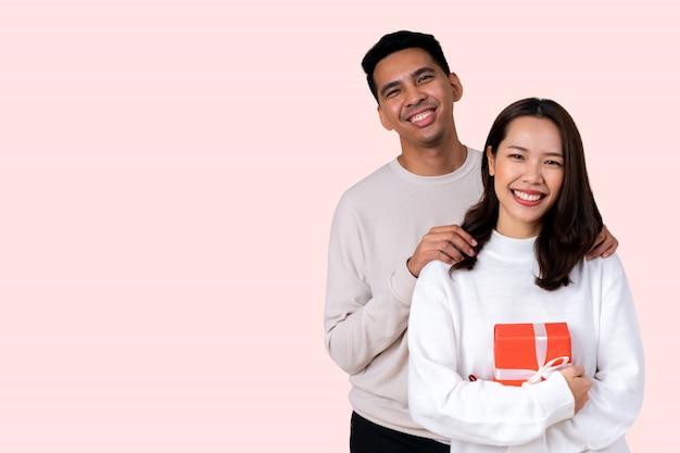 ラテン男はバレンタインデーのためのピンクの背景に分離された幸福笑顔でアジアの女性を受け入れる Premium写真