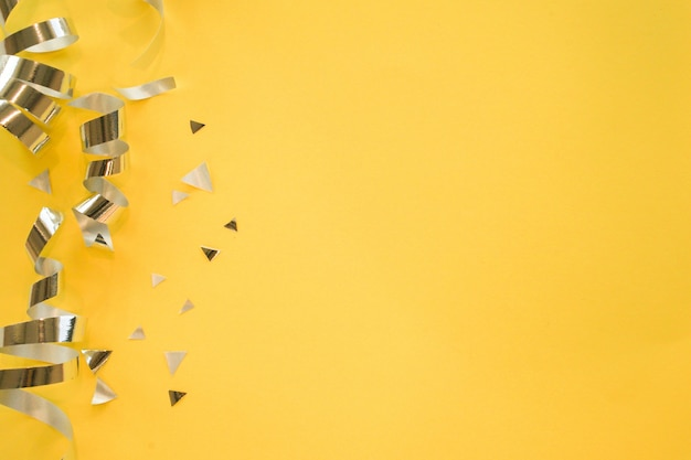 ローリングリボンと黄色の背景に紙吹雪のシルバー色 Premium写真