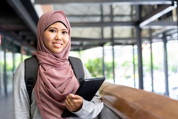 若い学生アジアのイスラム教徒の女性の笑みを浮かべて、教育概念の大学でタブレットを保持 Premium写真