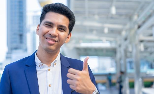 ラテン語のビジネスマンは、外の街の建物の背景で手ジェスチャー親指(良い兆候)を表示します。 Premium写真
