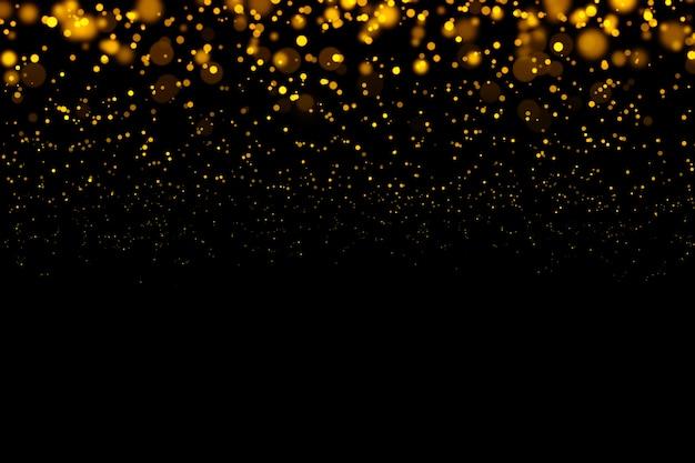 ゴールドのきらびやかな光ボケ抽象的な粒子が暗い背景に。 Premium写真