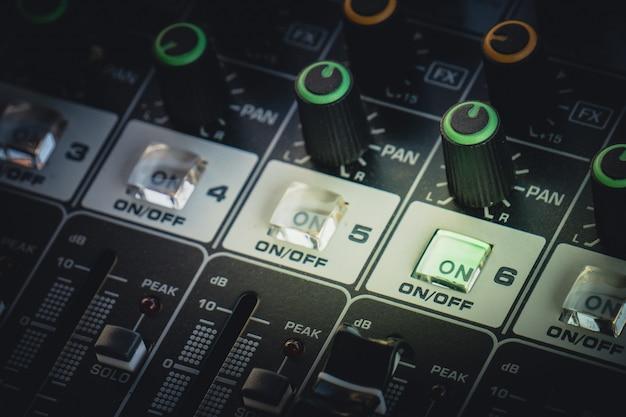 音を調整するノブとスライドバーを備えたプロフェッショナルオーディオミキサー Premium写真