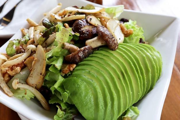 健康的なビーガンランチボウルを閉じます。マッシュルーム、アボカド、グリーンオーク、レッドオーク、ピーカンナッツ、木製テーブルのヘルシーソース付き。食品 Premium写真
