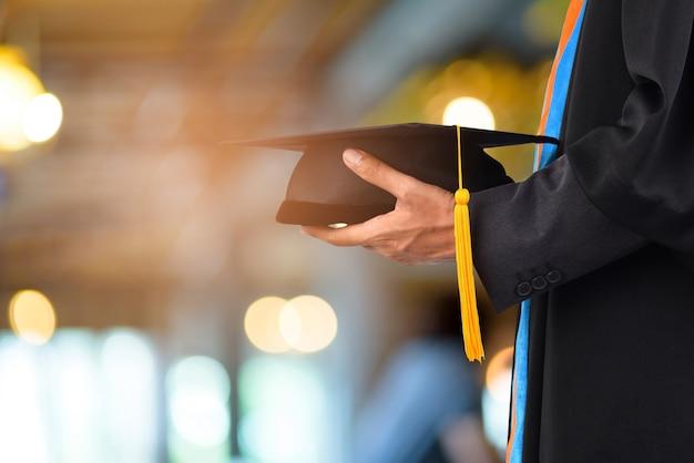 ボケのぼんやりした背景の前で、卒業は黒い黄色のタッセルを取る Premium写真