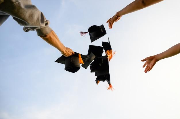 卒業生の黒い帽子を空に投げなさい。 Premium写真