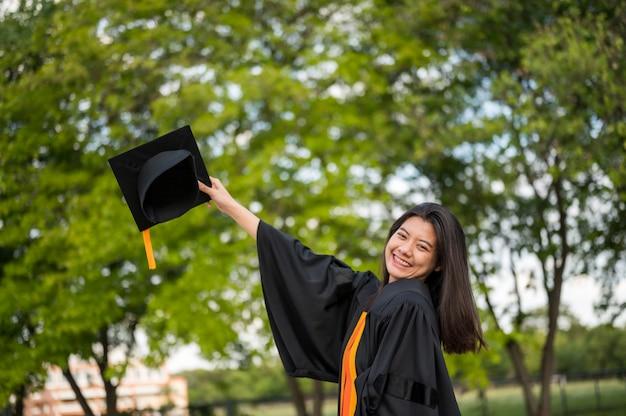 大学で卒業の喜びを表現する黒いフリルのドレスを着ている長い髪の女子学生。 Premium写真