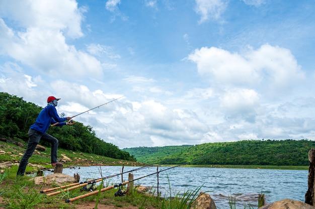 貯水池の釣り竿を持つ漁師 Premium写真