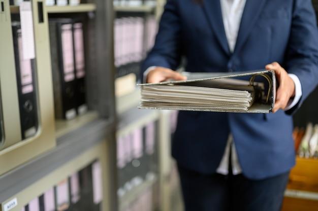 働く女性は何とかオフィス文書を見つける Premium写真
