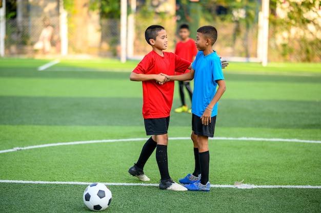 Мальчики играют в футбол на футбольном тренировочном поле Premium Фотографии