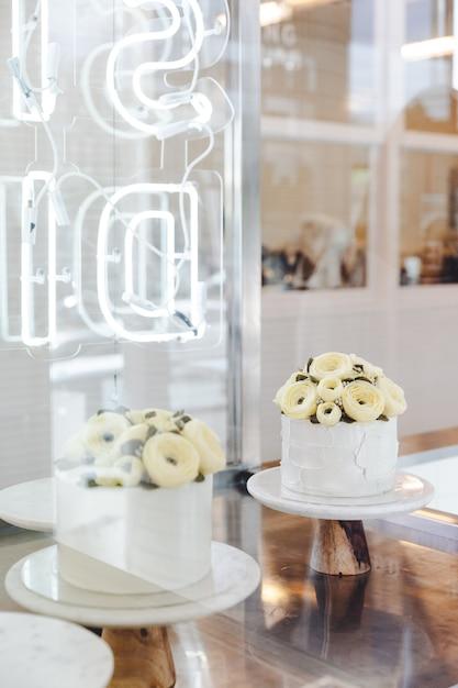 白いケーキのバタークリームの花が飾られています。 Premium写真
