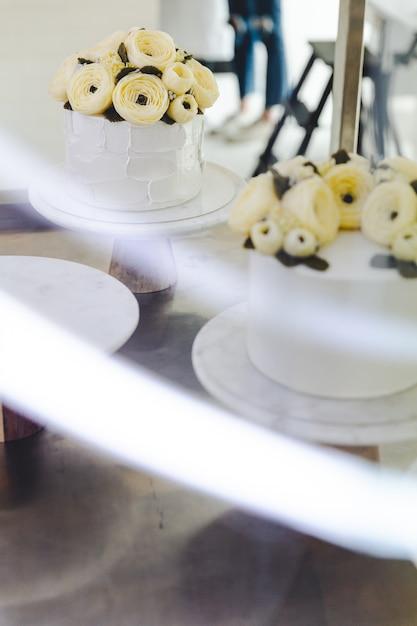 バタークリームの花と白いケーキは、フォアグラウンドで光の道とスタンドに飾られています。 Premium写真