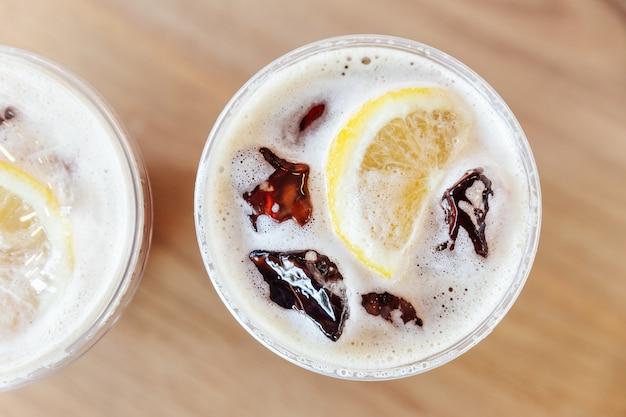 木製のテーブルにレモンとアイスニトロ冷たい醸造コーヒーのトップビュー Premium写真