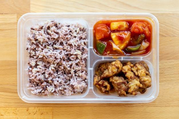 タイ風のオーガニックの甘酸っぱいの上から見ると、食品グレードのボックスで豚肉と米ベリーで揚げられました。 Premium写真