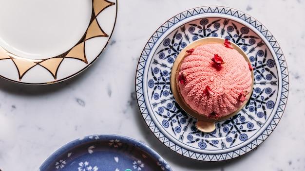 バラとライチのムースケーキは、青と白の磁器プレートのバラの花びらで飾られています。 Premium写真