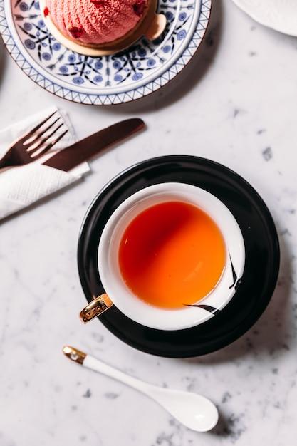 Вид сверху яблочного чая в фарфоровом стекле с тарелкой и ложкой, подается с муссами из роз и личи. Premium Фотографии