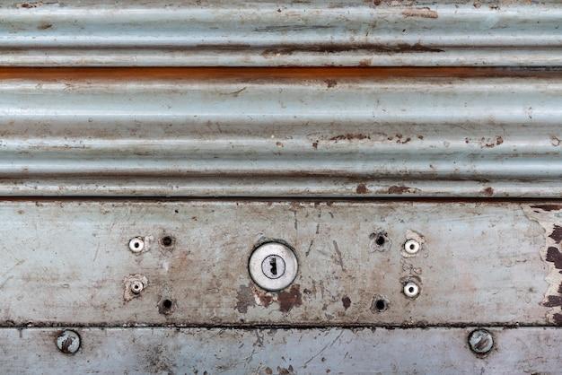 鍵穴付き鋼素朴なビンテージローリングドア。素朴なシャッタードアの質感。 Premium写真