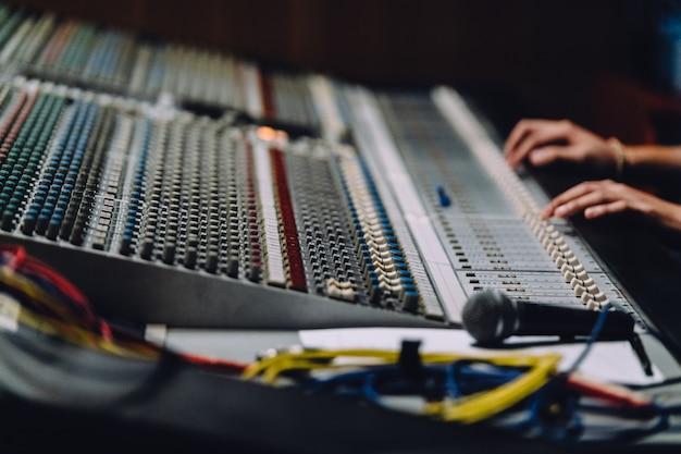 サウンドボード近くのプロの手がサウンドをミックスしている Premium写真