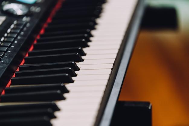 白と黒のキーで電子音楽キーボードシンセサイザーを閉じます。 Premium写真