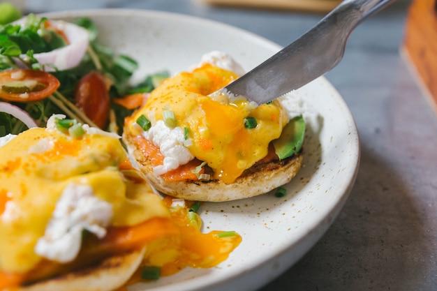 卵ベネディクトサーモンとアボカドをナイフで切って閉じ、白い皿にサラダを添えて。 Premium写真