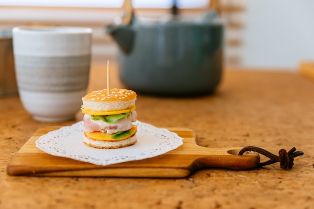 木製のまな板にミニチキンバーガーぼかしティーカップとバックグラウンドでマグカップ。 Premium写真