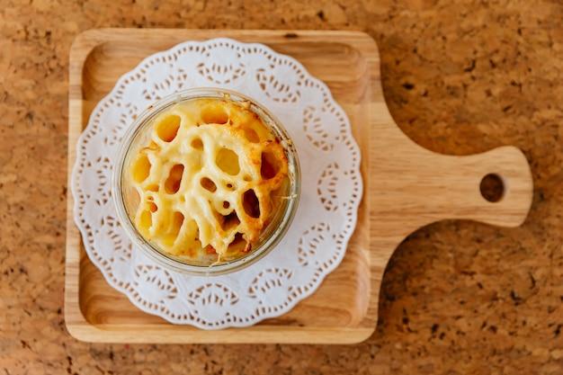 塩、コショウ、カトラリーと木の板にガラスのボウルにチーズ焼きペンネの平面図です。 Premium写真