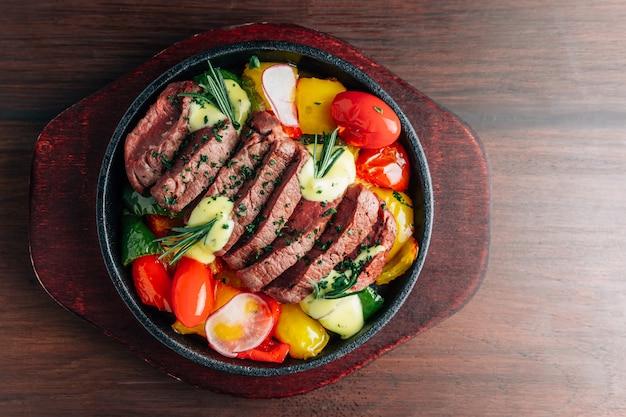 ミディアムレアビーフステーキの上面図は、トマト、ピーマン、大根、ローズマリーとホットプレートで提供しています。 Premium写真