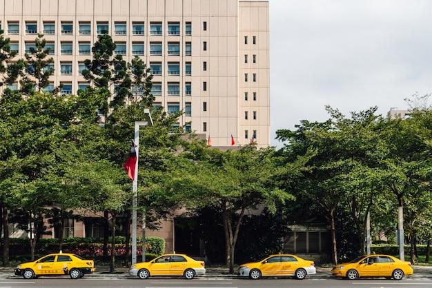 Четыре желтых такси ждут клиентов по улице в тайбэе, тайване. Premium Фотографии