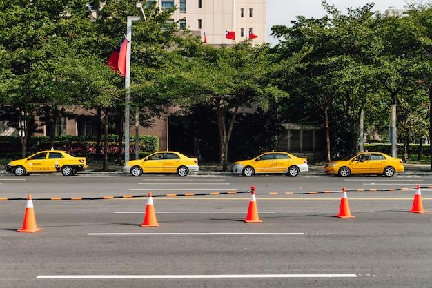 Четыре желтых такси ждут клиентов по улице, что возле парка с оранжевыми конусами. Premium Фотографии